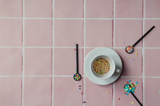 Tazza da caffè bianca piena di granelli di caramelle e cucchiai neri su uno sfondo di piastrelle rosa
