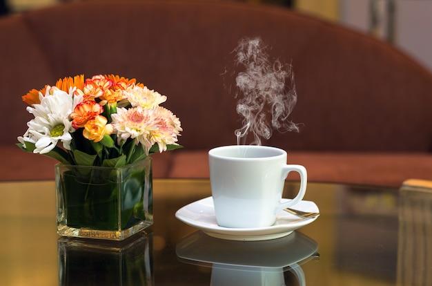 Tazza di caffè bianco sul tavolo di vetro con divano sfondo