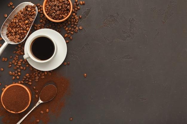 Tazza di caffè bianca sul piattino e fagioli arrostiti sparsi su fondo strutturato grigio, vista superiore. design minimalista per la pubblicità della caffetteria, copia spazio