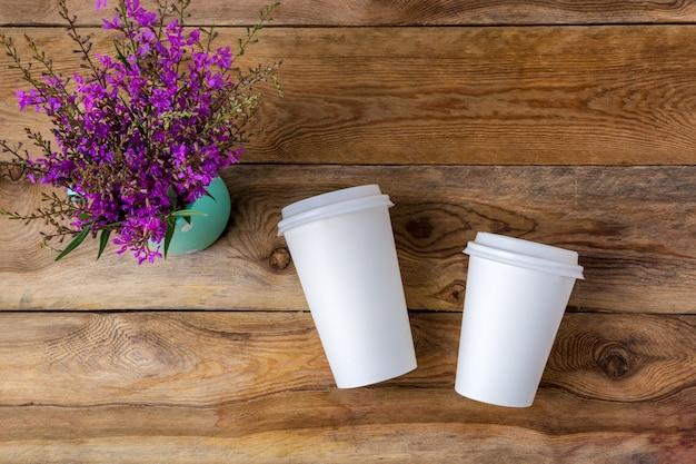 Bicchiere di carta calda usa e getta per caffè bianco con mockup coperchio con fiori di campo viola