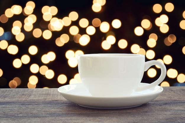 La tazza di caffè macchiato sul pavimento di legno marrone e ha fondo della luce del bokeh.