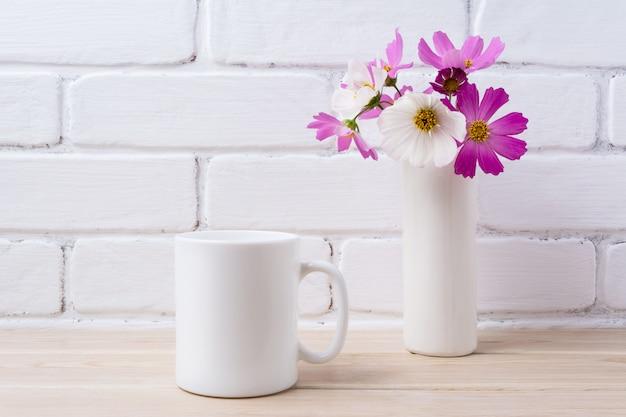 Mockup di tazza di caffè bianco con margherita bianca e rosa