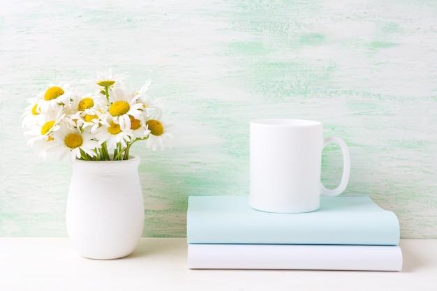 Tazza da caffè bianco con bouquet di camomilla di campo bianco in vaso e libri rustici fatti a mano