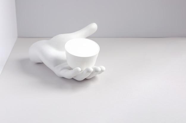 Composizione bianca con un barattolo di crema sulla mano in gesso nell'angolo.