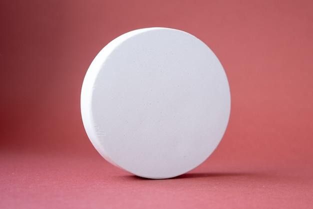 Piedistalli a forma di cerchio in cemento bianco su rosa rosso