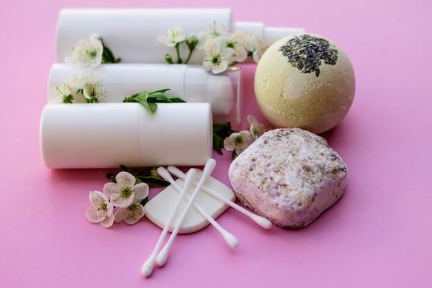 Bottiglie cosmetiche bianche, bomba da bagno, sapone fatto a mano, sale da bagno, spazzola per massaggi, spugna, cotton fioc con fiori di ciliegio su sfondo rosa. concetto di cosmetici biologici naturali.
