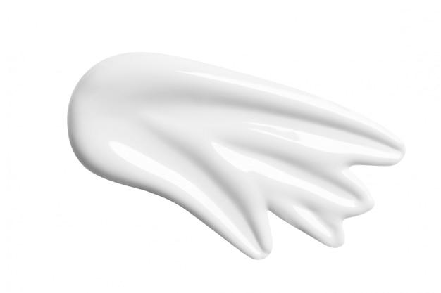 Macchia cosmetica bianca della lozione isolata su bianco