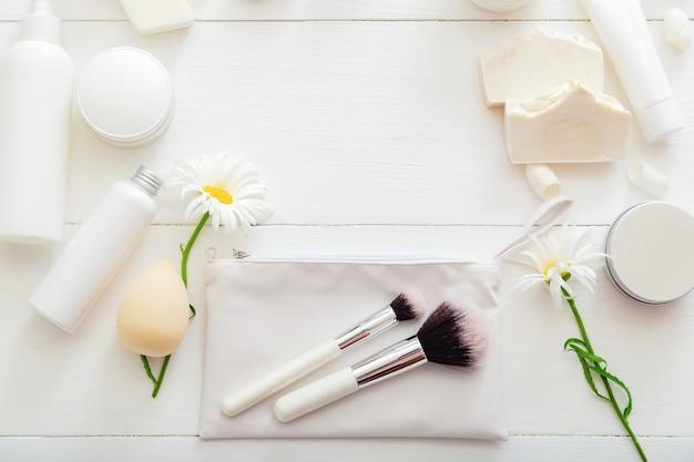 Prodotti cosmetici bianchi su un tavolo di legno con fiori come cornice per il trucco di bellezza pennelli per la cura della pelle