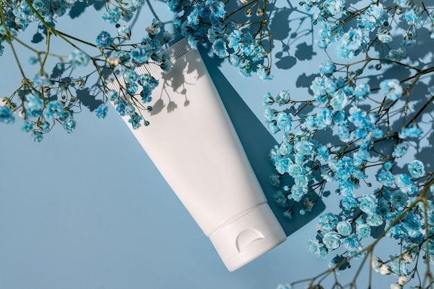 Tubo cosmetico bianco su sfondo blu con fiori di gipsofila. il concetto di una crema con ingredienti naturali e non testato sugli animali.