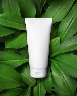 Tubo cosmetico bianco su sfondo di foglie