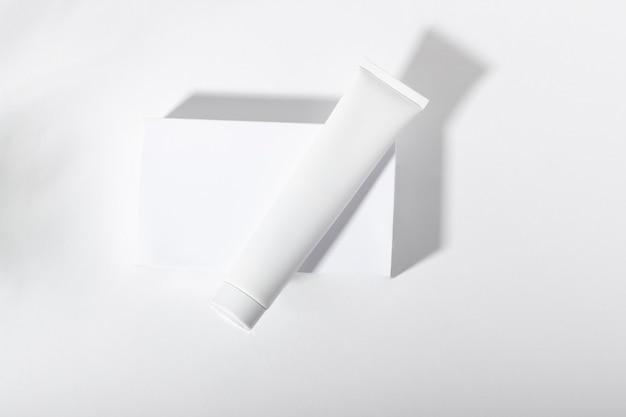 Tubo cosmetico bianco su supporto con foglie e ombre. dentifricio, crema viso e corpo. tubo cosmetico femminile con prodotto per la cura della pelle. cosmetici biologici. copia spazio.