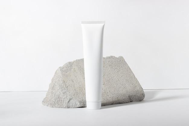 Tubo cosmetico bianco su sfondo bianco. una crema per il viso, crema per le mani o lozione nutriente e idratante. tubo cosmetico da donna con prodotto per la cura della pelle. cosmetici biologici, copia spazio sul lato destro