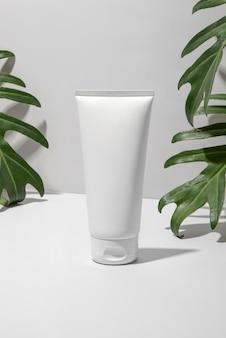 Tubo cosmetico bianco con foglie verdi su sfondo bianco. stile minimalista.