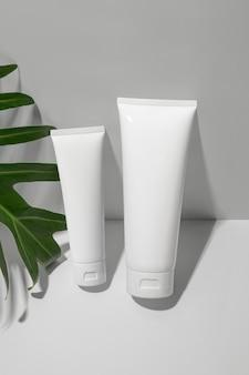 Tubi cosmetici bianchi con foglia verde su sfondo bianco. stile minimalista.