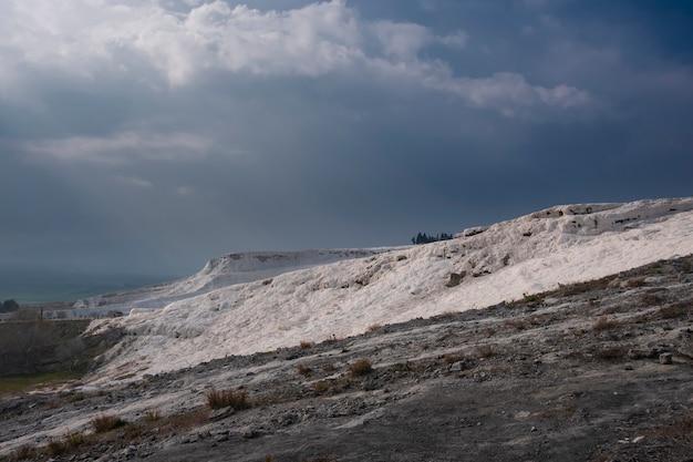 Montagna di cotone bianco pamukkale, in turchia sotto un cielo tempestoso
