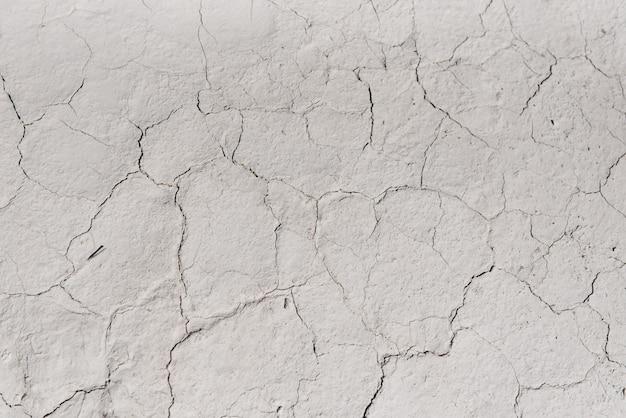 Trama di sfondo bianco incrinato, sfondo chiaro con graffio scuro, il terreno vicino alla cava di gesso, copia spazio