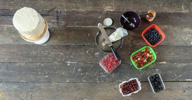 Base per torta alla crema bianca vicino a scatole con frutti di bosco e altri decori sul vecchio tavolo in legno, vista dall'alto