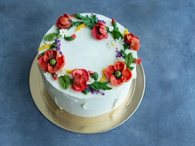 Torta di crema bianca decorata con fiori di crema di burro