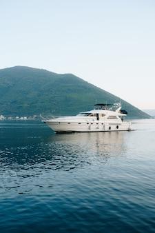 Yacht da crociera bianco sull'acqua vicino alle montagne in montenegro.