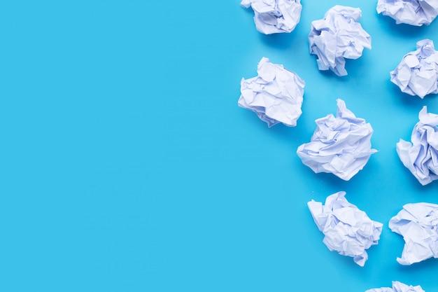 Sfere di carta sgualcite bianche su una priorità bassa blu.