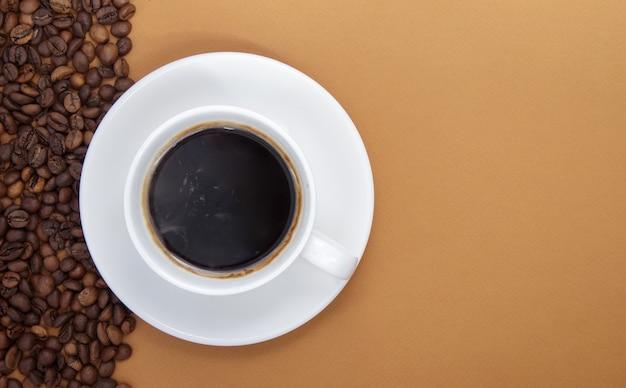 Tazza bianca di caffè nero americano senza latte con un mucchio di chicchi di caffè tostati sparsi da imballaggi di carta. sfondo caffè, vista dall'alto con spazio copia per logo o testo.