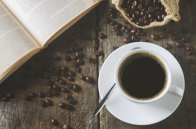 Tazza bianca di caffè nero sulla tavola di legno con chicchi di caffè e libro