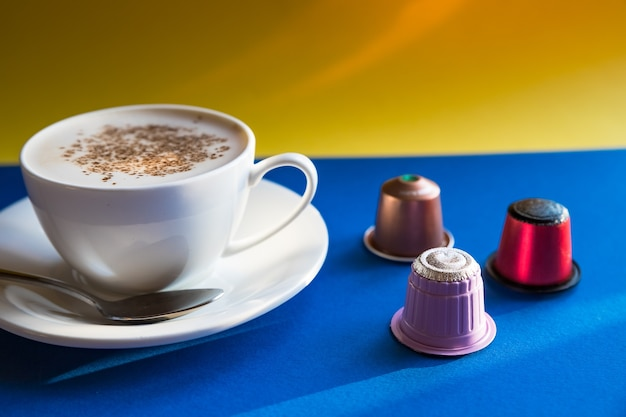 Tazza bianca di cappuccino, caffè espresso servito con cialde e capsule su sfondo blu. vista laterale. capsule per bevande per macchina da caffè