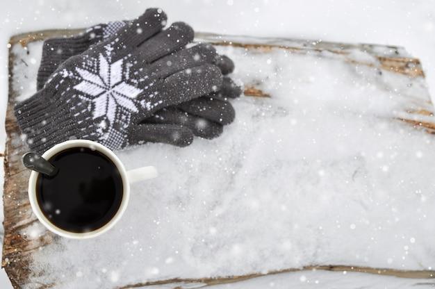 Una tazza di caffè bianca e guanti grigi lavorati a maglia con un modello su un banco di legno nella neve durante precipitazioni nevose.