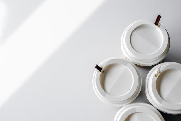 Tazza di caffè bianca sul fondo bianco della tavola. vista dall'alto. piatto