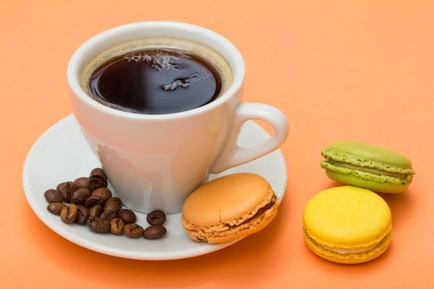 Tazza di caffè bianca con chicchi di caffè e deliziose torte di macarons di colore diverso con sfondo color pesca
