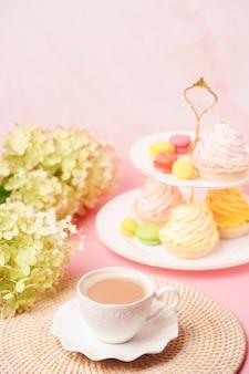 Una tazza di caffè bianca con un vaso di dolci e un mazzo di fiori in tenui colori pastello. congratulazioni per il tuo compleanno o per la festa della mamma.