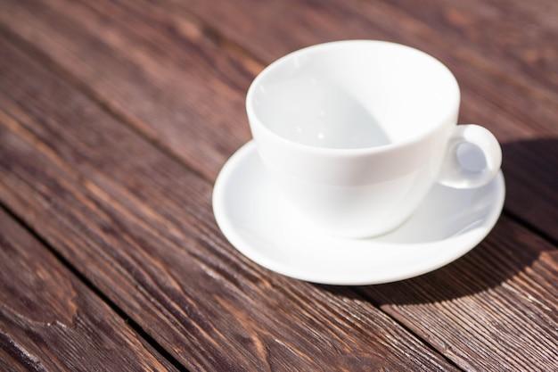 Tazza di caffè bianca sulla tavola di legno