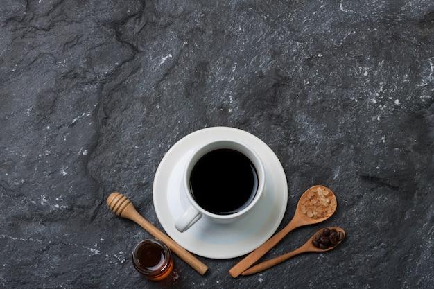 Caffè bianco della tazza bianca e chicco di caffè sullo zucchero del cucchiaio in cucchiaio di legno, miele sulla pietra nera