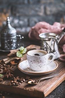 Tazza bianca di caffè espresso caldo gustoso fresco con chicchi di caffè