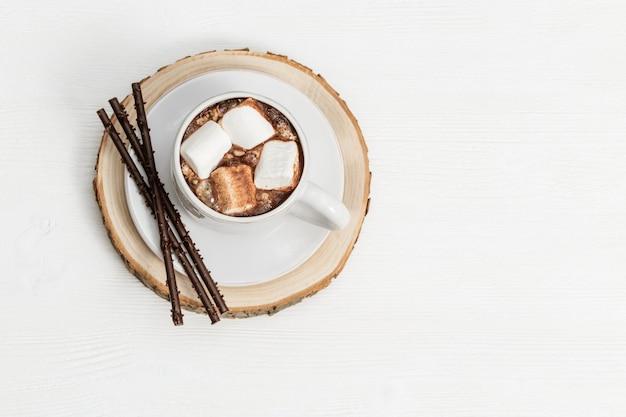 Tazza bianca di cioccolata calda con marshmallow e bastoncini di cioccolato
