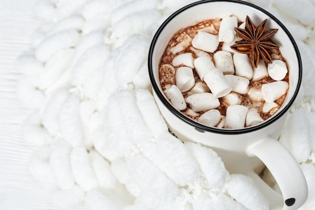 Tazza bianca di cioccolata calda con marshmallow su filato pompon