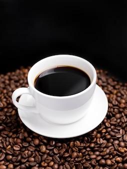 Tazza bianca di caffè caldo su una superficie scura con chicchi di caffè