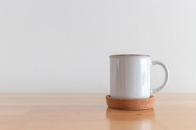 Tazza bianca della tazza di caffè caldo sulla tavola di legno con superficie bianca