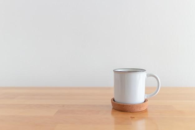 Tazza bianca della tazza di caffè caldo sulla tavola di legno con la parete bianca