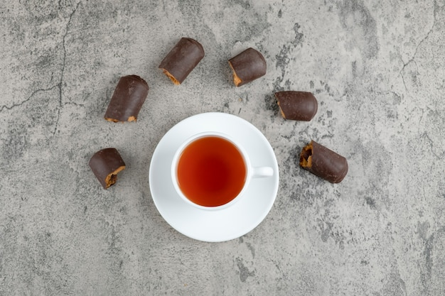 Una tazza bianca di tè caldo gustoso con bastoncini di cioccolato su un tavolo di marmo.