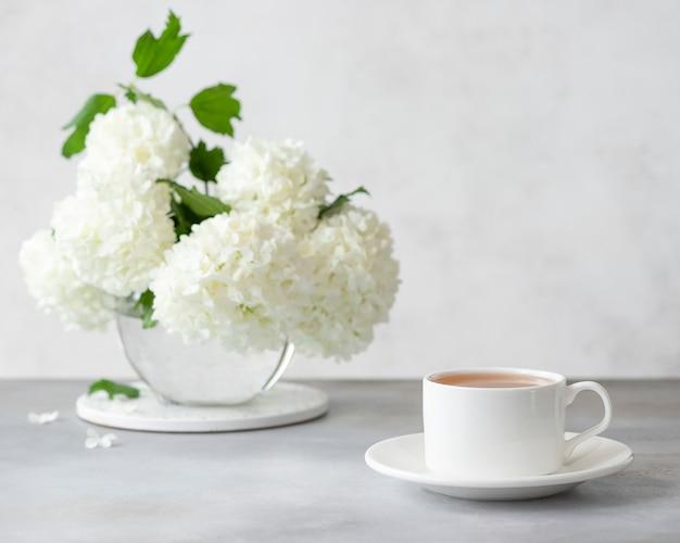 Una tazza bianca di tè caldo e un vaso con un bellissimo bouquet di fiori bianchi. l'ora del tè. monocromatico. immagine orizzontale. muro grigio chiaro con posto per il testo