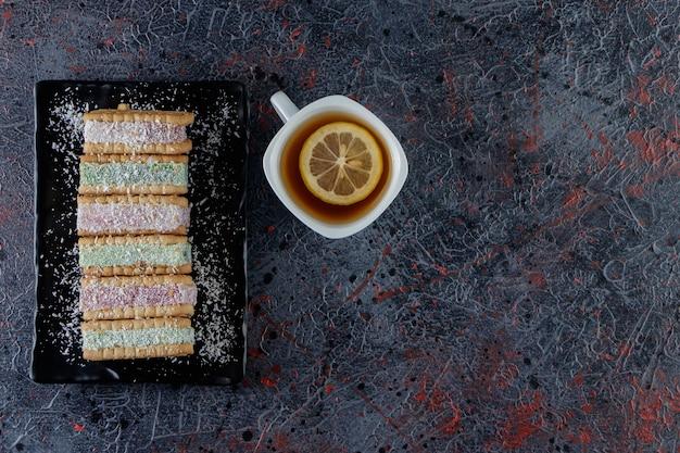 Una tazza bianca di tè caldo con un piatto nero di cialde dolci su uno sfondo scuro