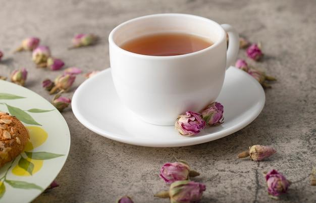 Una tazza bianca di tè caldo con biscotti e boccioli di rosa essiccati.