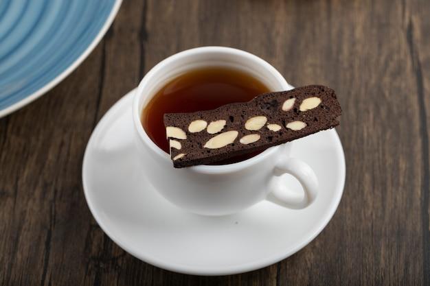 Una tazza bianca di tè caldo con la torta affettata posta sulla tavola di legno.