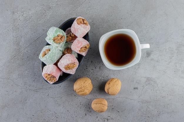 Una tazza bianca di tè caldo con delizie turche tradizionali e noci sane