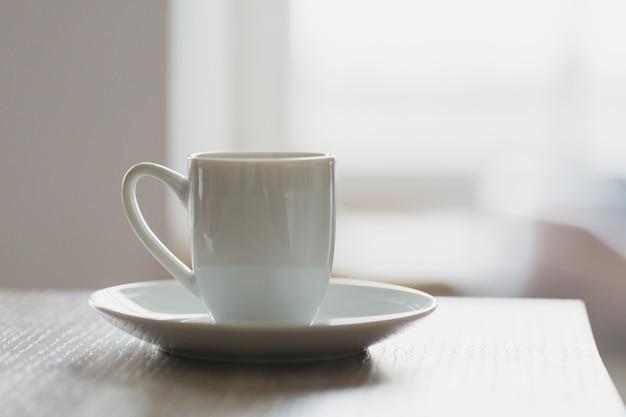 Bianco tazza di caffè del mattino sul tavolo contro la finestra