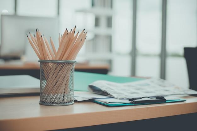 Una tazza bianca delle matite che impilano sullo scrittorio bianco con lo spazio della copia.