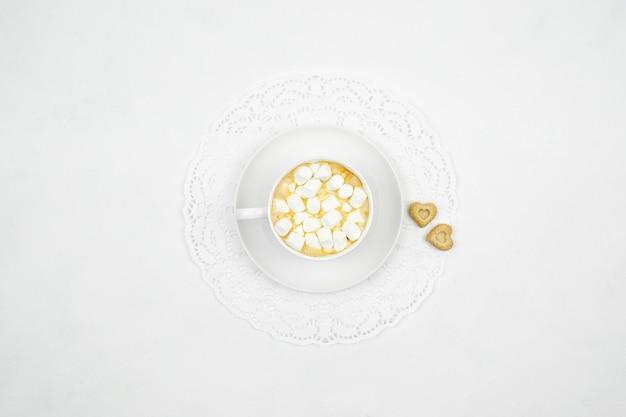 Una tazza bianca pf cappuccino con piccoli marshmallow su uno sfondo bianco