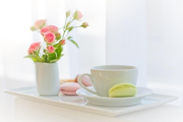 Tazza bianca, rose e amaretti vicino a una finestra.