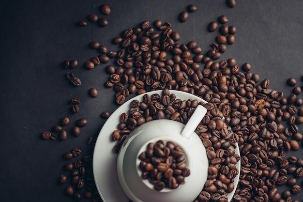Tazza e piattino bianchi e grandi chicchi di caffè su una fotografia macro scura.